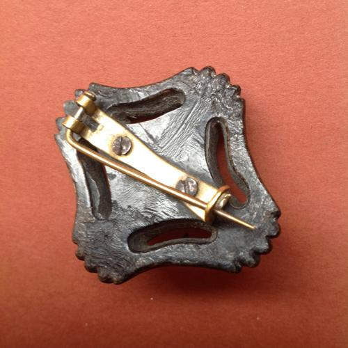 The reverse of a pressed horn brooch showing lamination and screw fittings. Whitby jet
